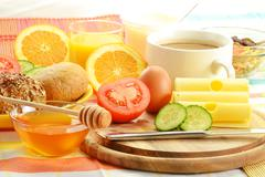 breakfast including rolls, egg, cheese, coffee and orange juice - stock photo