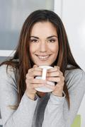 Stock Photo of woman at home sipping tea from a cup