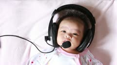 Baby enjoying to listen song - stock footage