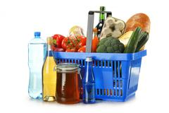 Composition with shopping basket and groceries isolated on white Stock Photos