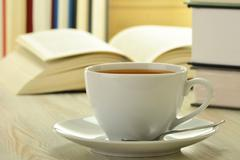 Books and cup of coffee on the table Stock Photos