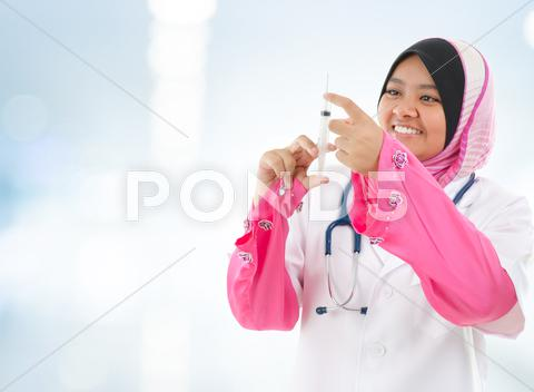 Stock photo of muslim doctor filling the syringe
