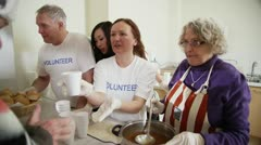 Soup kitchen volunteers help to feed the homeless Stock Footage