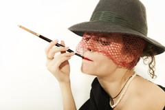 Young beautiful woman with cigarette in mouthpiece in hat with veil Stock Photos