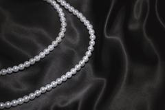 white pearl necklace on a black silk - stock photo