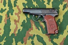 Army handgun on camouflaged background Stock Photos