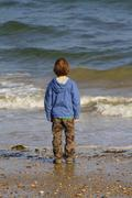 A child watching at the sea. Stock Photos