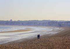 A couple strolling along Weymouth beach in April Stock Photos