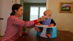 A mother wiping her babies mouth Stock Footage