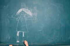 child drawing picture on chalkboard - stock photo
