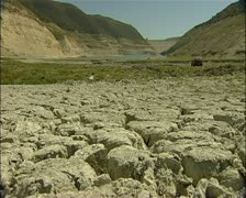 Dought in Cyprus - Kouris dam low angle dry cracked soil foreground 16:9 PAL Stock Footage