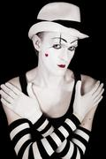 studio portrait of mime in white hat and striped gloves - stock photo