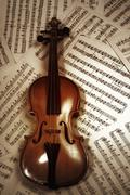 Stock Photo of old wood violin lying on musical notes