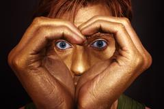 Man's face with her hands folded in the shape of a heart Stock Photos