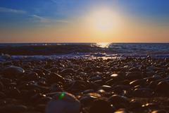 Stock Photo of sunset on the beach stone
