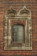 window with ornament in the brick wall - stock photo