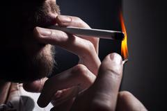 Men's hand lights cigarette with a match Stock Photos