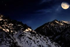 mountain winter landscape with yellow moon - stock photo