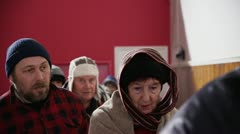Homeless and needy people, wrapped up warm against the cold are standing in line Stock Footage