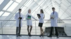 Two pairs of young successful doctors men and women Stock Footage