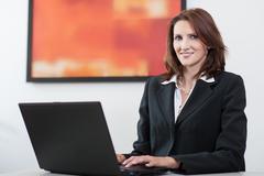 Businesswoman uses laptop Stock Photos