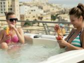 Happy girlfriends drinking cocktails in jacuzzi NTSC Stock Footage
