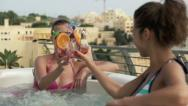 Girlfriends raising toast with drinks in jacuzzi, slow motion, shot at 240fps HD Stock Footage