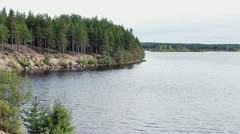 Lake with shore in evergreen forests of Karelia in Russia Stock Footage