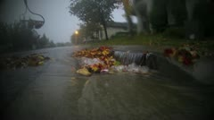RAKING FLOODING STORM DRAINS FLOOD IN RAIN CLOGGED GUTTERS LEAVES NEIGHBORHOOD Stock Footage