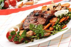Meat with vegetables and greens - prepared and served meal Stock Photos