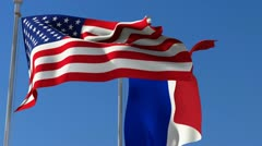 Flag of  France and USA waving in the wind against blue sky. Stock Footage