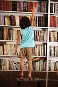 kid trying to reach a book in the library - stock photo