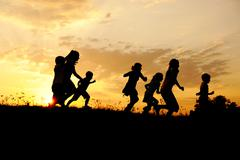 silhouette, group of happy children playing on meadow, sunset, summertime - stock photo