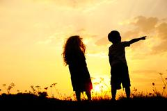 Silhouette, group of happy children playing on meadow, sunset, summertime Stock Photos
