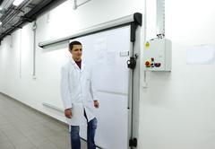 young worker opening  door of industrial refrigerator - stock photo