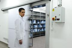 Young worker opening  door of industrial refrigerator Stock Photos