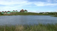 Traditional African Xhosa huts by a lake in the Transkei Stock Footage