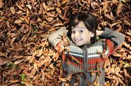 Stock Photo of a little child playing in the autumn leaves