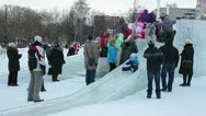 Children with parent move down from ice slide Stock Footage