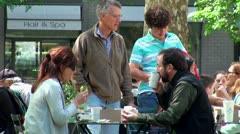 Family eats at the summer outdoor cafe in Madison Square Park. NYC, USA Stock Footage