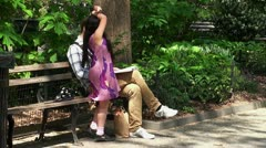 Father reading a book to her daughter in Madison Square Park. NYC, USA. Stock Footage