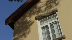 Mottled shadows of trees on window wall.Tree with old house,blue sky &amp. Stock Footage