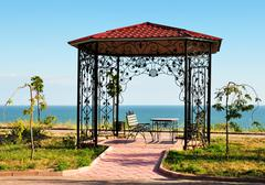 Summer-house with bench and sea on background Stock Photos