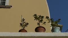 Flower pots on balcony shaking in wind & blue sky.looking up angle. Stock Footage