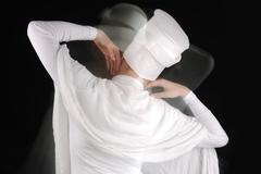 sufi female dancing, white on black, motion blur - stock photo