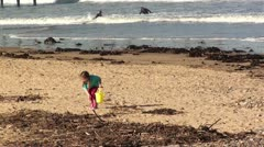 Little girl with bucket and spade on sand Stock Footage