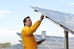 young expert working at solar panels - stock photo