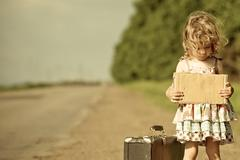 Lonely girl with suitcase standing about road Stock Photos