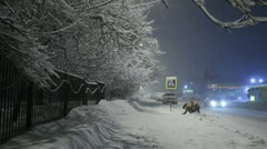 Two yard keepers clean the sidewalk in the evening during a heavy snowfall Stock Footage