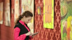 A beautiful young girl looking at the pictures in the gallery Stock Footage